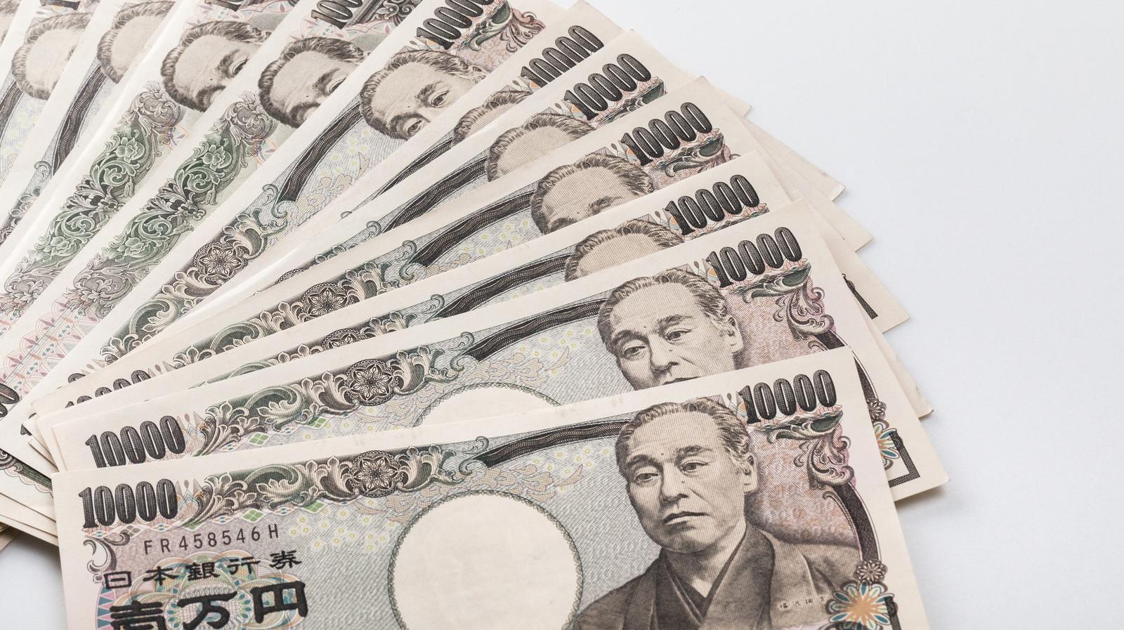 複数枚ある1万円札をきれいに並べている。